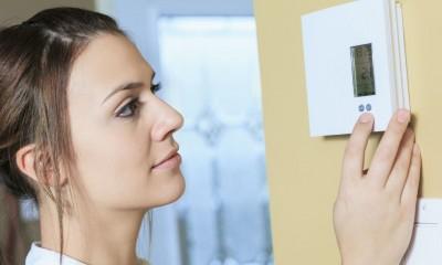 Frau mit Thermostat - intelligente Heimvernetzung für Klima und Heizung
